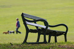 Park bench and dog walker. Park bench with a dog walker in the background stock photo