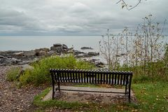 Park bench facing rocky shore of Lake Superior in Northern Minnesota on a cloudy day. Wonderful travel destination are the public parks along the rocky shore of stock photo