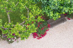 Park bench with flowers and path from above. Birds eye view of park bench and flowers Royalty Free Stock Image