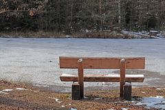 Park Bench. A park bench in front of a frozen lake stock photos