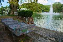 Park Bench. A garden bench beside a pond in the park. Hatyai, Songkhla, Thailand Royalty Free Stock Image