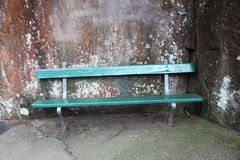 Park bench in green against a natural stone wall Stock Image
