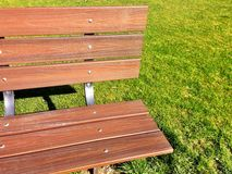 Park Bench and Green Grass with Shadow. Brightly lit park bench with grassy background stock photos