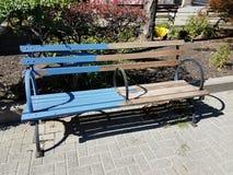 Park bench half painted blue. Wood park bench half painted blue and half plain wood stock photos