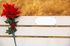 Park Bench Memorial. A park bench with a plate ready for your inscription decorated with a Christmas bouquet Stock Photos
