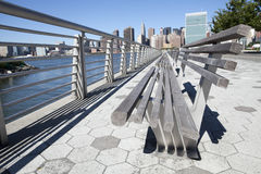 Park Bench with NYC skyline. This picture was taken in Gantry Park in Queens, it looks along the benches directly at the skyline of NYC skyline, including the Royalty Free Stock Images