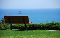 Park bench with ocean view. A park bench with an exceptional view of the pacific ocean. Bench is in Focus, Ship is not Stock Images