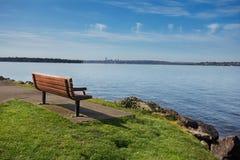 Park bench overlooking Lake Washington. Bench at a lakeside park overlooking Lake Washington in Spring sunshine royalty free stock image