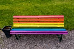 Park bench painted in the vibrant pride colors. Park bench in vibrant pride colors. Painted in the colorful horizontal striped rainbow pattern royalty free stock photography