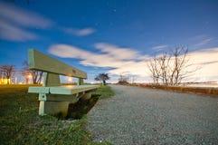 Park bench on path. Night photo Royalty Free Stock Photo