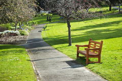 Park bench and path leading to out of focus figure Stock Photo