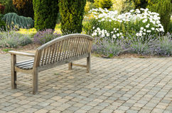 Park bench on paved walk Royalty Free Stock Photo