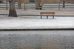Park Bench by Pond In Winter snow Stock Image
