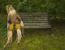 Park Bench Scarecrow. Happy scarecrow sitting on an old, rusty, scaley park bench Stock Photo