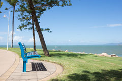Park bench with sea views. Empty blue park bench seat looking out to sea on a sunny day Royalty Free Stock Images