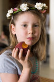 Young girl eating peach. Pretty girl with flowers in hair eating fruit Royalty Free Stock Image