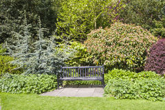 Park bench set in beautiful gardens stock images