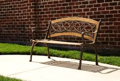 Park bench on sidewalk. With brick wall behind it stock images