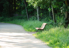 Park bench in silence. Wooden park bench in the afternoon sun Royalty Free Stock Photo