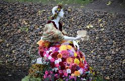 Statue of a woman dressed in flowers reading a book on a bench near the pond royalty free stock image