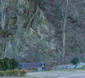 Park bench sitting at the foot of a mountain Stock Images