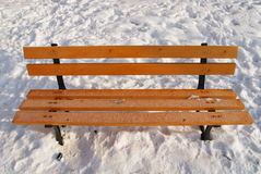 Park bench on snow. Bench in city park arounded by snow Stock Photo