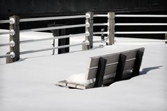 Park Bench in the Snow. Black and white park bench in the winter covered in snow Stock Images