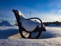 A park bench after a snowfall. This park bench was surprised by the snow, the morning the day rose on a beautiful day. Photo taken at Acton Vale, Quebec, Canada Royalty Free Stock Photos