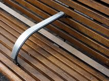 Park Bench. Stainless steel rail on stained wood park bench in public place, area Royalty Free Stock Photos