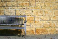 Park bench and stone wall. Royalty Free Stock Images