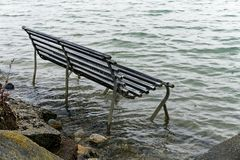 Park bench swamped by a rising sea level stock images