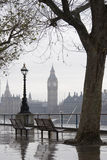 Park bench on the thames overlooking big ben Stock Image