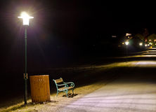 Park bench and trash container  illuminated by a lantern Royalty Free Stock Photo