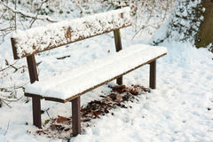 Park bench under pack of snow Stock Photos