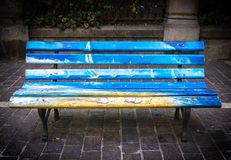 Bench painted in the park. Park bench in vibrant pride colors royalty free stock images