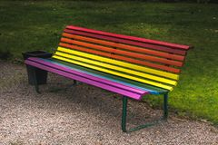 Park bench in vibrant pride colors. Painted in the horizontal striped rainbow pattern located in Storvik Sweden stock images