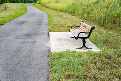 Park Bench by a Walking Path. A park bench located by a walking path Royalty Free Stock Photos