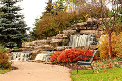 Park bench and waterfall Royalty Free Stock Photos