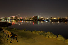 Park Bench on Waterfront at Night. A park bench sits by the water at night with city lights in background Royalty Free Stock Image