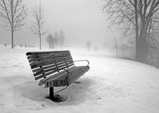 Park Bench in Winter Fog. Wooden park bench surrounded by moody fog in winter; black and white Royalty Free Stock Photos