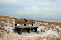 Park Bench in the Winter. This is located on a trail at Ludington State Park, in Ludington Michigan.  The trail features Dunes, Big Sable Lighthouse, and Lake Stock Photo