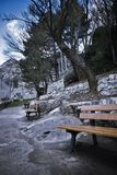 Park Benches. View of rocky landscape with pathway leading away and vacant benches Stock Photo