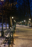 Park benches in park at night. Park benches in Planty park at night, in distance blurred people Royalty Free Stock Photos