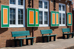 Park benches and pattens. Green park benches create an interesting pattern under green and orange shutters on a brick street Stock Photos