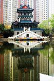 Old building and modern building of china in the park. In the park ,besaid the lake, a old building is here and it is background is modern building Royalty Free Stock Images