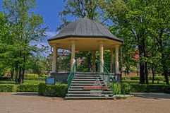Park bower. The photo shows the gazebo situated in the city park. Round columns are supported by a domed roof. The stairs lead stone stairs. In front of the Royalty Free Stock Photo