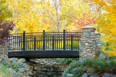 Park Bridge. A bridge through the park in the autumn, surrounded by colorful trees and bushes Royalty Free Stock Photography