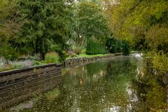 Park Canal in Stratford Ontario. A canal running through a park in Stratford Ontario. The trees are different shades of green and there is a stone wall retaining stock photos