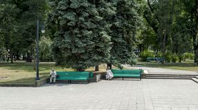 In the park - Chisinau. A gentleman and a lady sitting on two benches in the park, Chisinau, Kisinev Moldova, center of city royalty free stock images