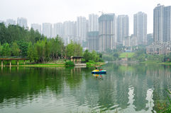 Park Among City Buildings. A small park with green trees and a foggy lake is located among city buildings. Taken in Rongqiao Park, Chongqing, China Royalty Free Stock Photo